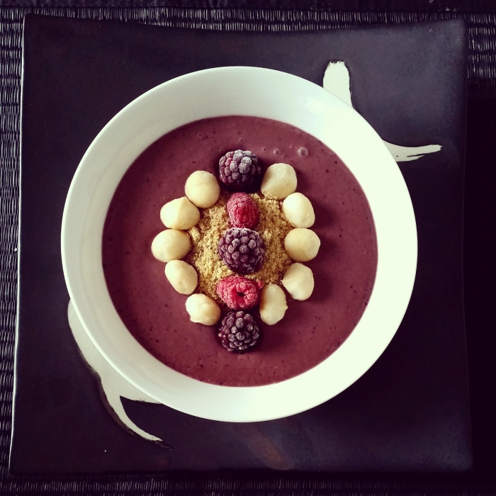 Red velvet smoothie bowl topped with golden linseed, macadamia nuts and frozen berries - heavenly!
